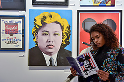 "© Licensed to London News Pictures. 06/10/2017. London, UK.  A woman sits beside ""Kim Jong-Un"", 2016, by Cartrain at the Moniker Art Fair, the world's biggest urban art fair, taking place at the Old Truman Brewery in East London from 5 to 8 October 2017.  The fair brings together the world's most influential new-contemporary and urban art galleries to show international artworks to Londoners. Photo credit : Stephen Chung/LNP"