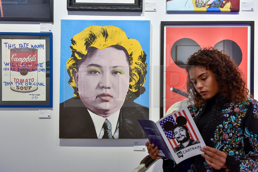 """© Licensed to London News Pictures. 06/10/2017. London, UK.  A woman sits beside """"Kim Jong-Un"""", 2016, by Cartrain at the Moniker Art Fair, the world's biggest urban art fair, taking place at the Old Truman Brewery in East London from 5 to 8 October 2017.  The fair brings together the world's most influential new-contemporary and urban art galleries to show international artworks to Londoners. Photo credit : Stephen Chung/LNP"""