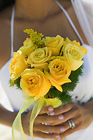 Bride holding yellow rose bouquet (close-up)