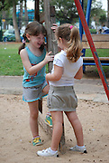 Two preschool girls of 5 playing in a playground
