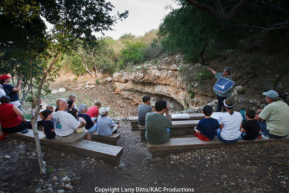 Visitor listen to Vicki Ritter, Steward at The Nature Conservancy's Eckert James River Bat Cave Preserve near Mason, Texas as she discusses the cave and its bats.  She leads nature walks and offers interpretive seminars on the cave and its wildlife like the Mexican Free-tailed Bat.