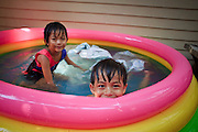 "Mar 23, 2009 -- BANGKOK, THAILAND: Children play in an inflatable pool in front of their home in Ban Krua. The Ban Krua neighborhood of Bangkok is the oldest Muslim community in Bangkok. Ban Krua was originally settled by Cham Muslims from Cambodia and Vietnam who fought on the side of the Thai King Rama I. They were given a royal grant of land east of what was then the Thai capitol at the end of the 18th century in return for their military service. The Cham Muslims were originally weavers and what is known as ""Thai Silk"" was developed by the people in Ban Krua. Several families in the neighborhood still weave in their homes.     Photo by Jack Kurtz"