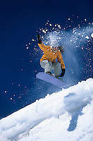 Snowboarder mid-air above ski Slope snow powder trailing behind