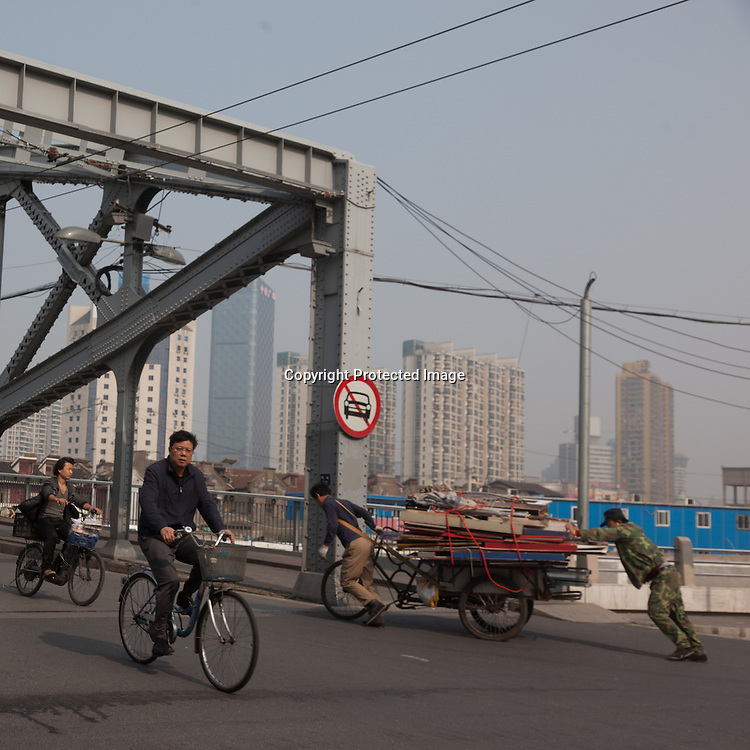 China, Shanghai. Hongkou and north shanghai area. pedestrians and vehicles .old bridge on Wusong river