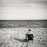 Elderly man sitting alone in a chair sunbathing at the Los frailes beach in Parque Nacional Cabo Pulmo, Baja California at easter holliday