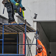 Workers assembling scaffolding to the top and around the outside of Lenox Health Greenwich Village building.<br />
