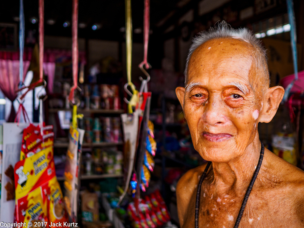 """20 JUNE 2017 - BANGKOK, THAILAND:   A shopkeeper in a community along the Chao Phraya River south of Krung Thon Bridge. This is one of the first parts of the riverbank that is scheduled to be redeveloped. The communities along the river don't know what's going to happen when the redevelopment starts. The Chao Phraya promenade is development project of parks, walkways and recreational areas on the Chao Phraya River between Pin Klao and Phra Nang Klao Bridges. The 14 kilometer long promenade will cost approximately 14 billion Baht (407 million US Dollars). The project involves the forced eviction of more than 200 communities of people who live along the river, a dozen riverfront  temples, several schools, and privately-owned piers on both sides of the Chao Phraya River. Construction is scheduled on the project is scheduled to start in early 2016. There has been very little public input on the planned redevelopment. The Thai government is also cracking down on homes built over the river, such homes are said to be in violation of the """"Navigation in Thai Waters Act."""" Owners face fines and the possibility that their homes will be torn down.              PHOTO BY JACK KURTZ"""