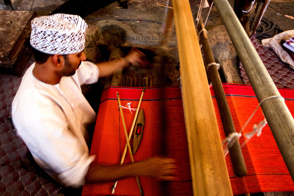 Oman, village of Samad, home of traditional pit weavers.  Weaver at work on a length of red silk, seen from above since he sits in a hole in the ground.  His hands and arms show motion blur from throwing the shuttle.