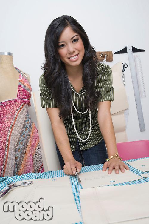 Portrait of female fashion designer working at desk