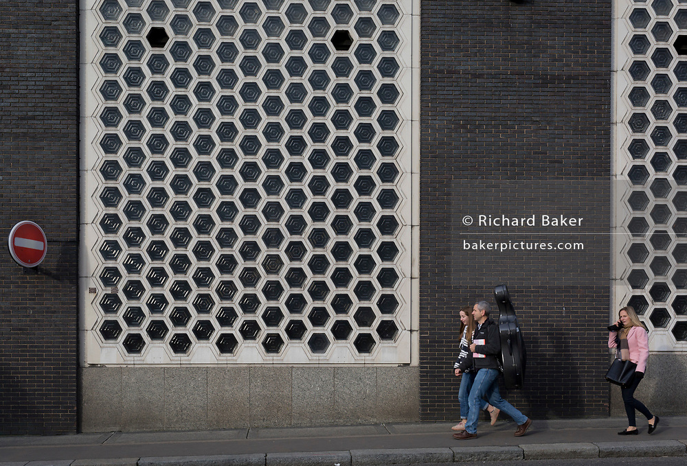 Pedestrians walk beneath a glass tile wall of the former Smithfield meat market, on 20th November 2019, at Smithfield in the City of London, England. In March 2015, the Museum of London revealed plans to vacate its Barbican site and move into the General Market Building. The cost of the move is estimated to be in the region of £70 million and, if funding can be achieved, would be complete by 2021. There has been a market on this location since the Bartholomew Fair was established in 1133 by Augustinian friars.
