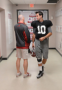 Equipment managers work in the Mal Moore Athletic Facility to get the University of Alabama football team ready for the trip to Baton Rouge to face LSU.  Equipment manager Jeff Springer talks to quarterback AJ McCarron in the hallway before practice.  Photo by Gary Cosby Jr.