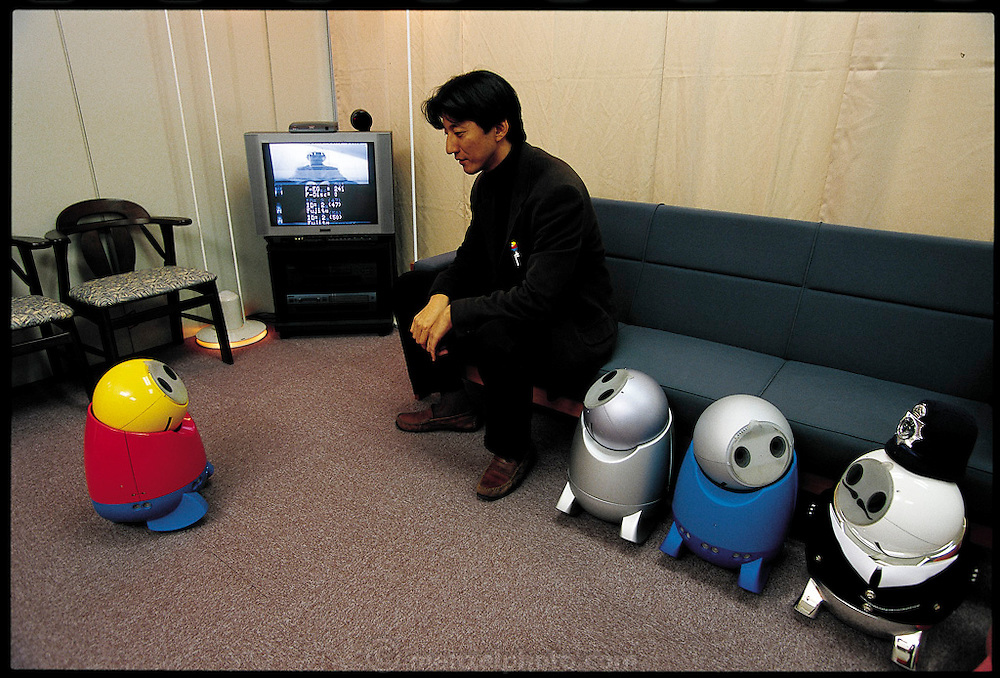 Robot designer Yoshihiro Fujita stares into the electronic eyes of R100, his personal-assistant robot. The robot can recognize faces, identify a few hundred words of Japanese, and obey simple commands, but its most important job, Fujita says, is to help families keep in touch. If Mom at work wants to remind Junior at home to study, she can E-mail the robot, which will deliver the message verbally. To take the sting out of the command, the robot can sing and dance, a charming feature that is one reason NEC is inching toward commercializing the project. Japan. From the book Robo sapiens: Evolution of a New Species, page166-167.