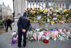 © Licensed to London News Pictures. 27/03/2017. London, UK. A police officer pays his respects to the victims of Westminster terror attack outside the Houses of Parliament in London on Monday, 27 March 2017. Photo credit: Tolga Akmen/LNP