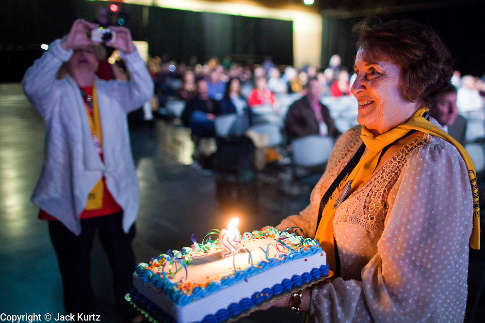 27 FEBRUARY 2011 - PHOENIX, AZ: A woman carries a candle lit birthday cake marking the second anniversary of the Tea Party movement through the hall at the Tea Party Patriots American Policy Summit in Phoenix Sunday, the last day of the conference. About 2,000 people were expected to attend the event, which organizers said was meant to unite Tea Party groups across the country. Speakers included former Minnesota Governor Tim Pawlenty, Texas Congressman Ron Paul, former Clinton advisor Dick Morris and conservative blogger Andrew Brietbart. The event ended with a presidential straw poll, which was won by Herman Cain, a newspaper columnist from Atlanta, GA.     Photo by Jack Kurtz
