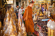 """05 JULY 2011 - BANGKOK, THAILAND:      A Buddhist monk and nun walk through shop selling Buddhist paraphernalia on Bamrung Muang Street in Bangkok. Thanon Bamrung Muang (Thanon is Thai for Road or Street) is Bangkok's """"Street of Many Buddhas."""" Like many ancient cities, Bangkok was once a city of artisan's neighborhoods and Bamrung Muang Road, near Bangkok's present day city hall, was once the street where all the country's Buddha statues were made. Now they made in factories on the edge of Bangkok, but Bamrung Muang Road is still where the statues are sold. Once an elephant trail, it was one of the first streets paved in Bangkok, it is the largest center of Buddhist supplies in Thailand. Not just statues but also monk's robes, candles, alms bowls, and pre-configured alms baskets are for sale along both sides of the street.       PHOTO BY JACK KURTZ"""