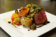A 28-day-aged New York strip with grilled eggplant caponata, tomato confit, olive aioli and roasted garlic is one of the items on the seasonal menu Friday, Sept. 7, 2007 at the Lincoln Cafe in Mount Vernon, Iowa. Photo by Scott Morgan
