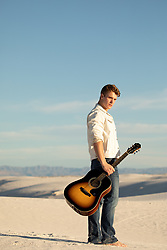 man with a guitar on a sand dune
