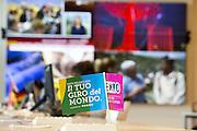 Two little flags on the tables of the press room at Expo 2015, Rho-Pero, Milan, June 2015. The flag says &quot;your world tour.&quot; TV screens in the background. &copy; Carlo cerchioli<br /> <br /> Due bandierine sui tavoli della sala stampa a Expo 2015, Rho-Pero, Milano, giugno 2015. La bandierina dice &quot;il tuo giro del mondo&quot;. Sullo sfondo schermi televisivi.