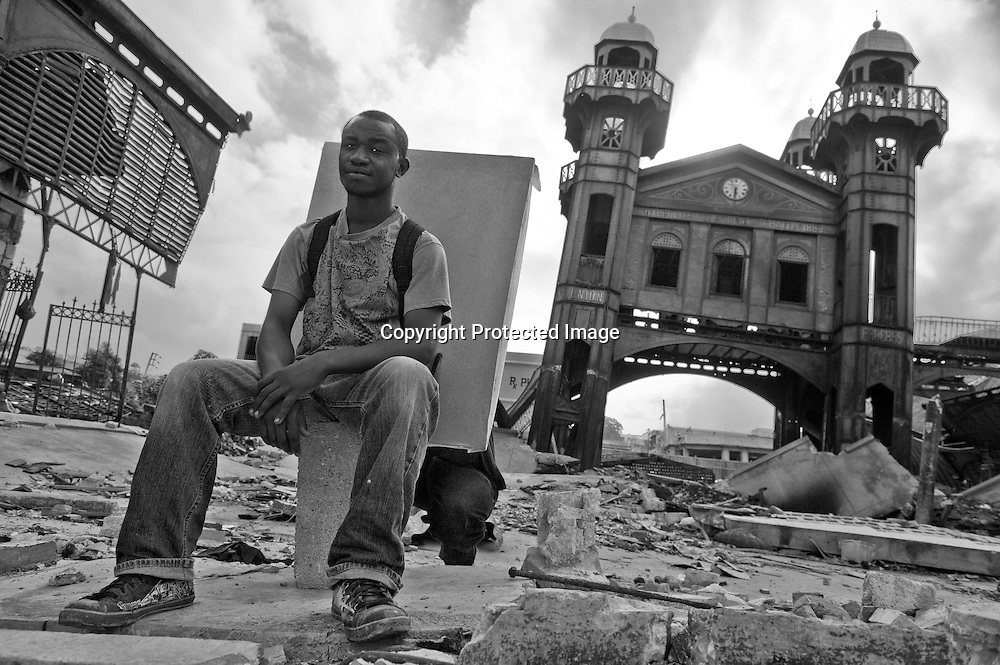 "Orestal Jacky, 24, takes up a perch on the fallen roof of the Hypollite Iron Market, directly above the spot where he would normally be selling handcrafts and paintings. After the quake shook, he saw smoke and darted outside before the building collapsed. ""I'm always here,"" he says, ""but there's no business."" His inventory is still under the rubble. He lost two members of his family, and the future is uncertain. ""I'm still scared. I don't know what is going to happen."""