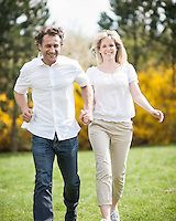 Couple running through park holding hands