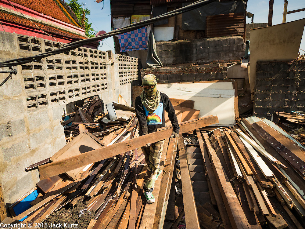 12 NOVEMBER 2015 - BANGKOK, THAILAND:  A demolition worker tears down a home at Wat Kalayanmit. Fifty-four homes around Wat Kalayanamit, a historic Buddhist temple on the Chao Phraya River in the Thonburi section of Bangkok, are being razed and the residents evicted to make way for new development at the temple. The abbot of the temple said he was evicting the residents, who have lived on the temple grounds for generations, because their homes are unsafe and because he wants to improve the temple grounds. The evictions are a part of a Bangkok trend, especially along the Chao Phraya River and BTS light rail lines. Low income people are being evicted from their long time homes to make way for urban renewal.       PHOTO BY JACK KURTZ
