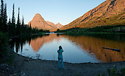 """Rising Wolf Mountain (9513 feet/2899 meters) and Sinopah Mountain (left) reflect in Pray Lake, in Glacier National Park, Montana, USA. Since 1932, Canada and USA have shared Waterton-Glacier International Peace Park, which UNESCO declared a World Heritage Site (1995) containing two Biosphere Reserves (1976). Rocks in the park are primarily sedimentary layers deposited in shallow seas over 1.6 billion to 800 million years ago. During the tectonic formation of the Rocky Mountains 170 million years ago, the Lewis Overthrust displaced these old rocks over newer Cretaceous age rocks. Glaciers carved spectacular U-shaped valleys and pyramidal peaks as recently as the Last Glacial Maximum (the last """"Ice Age"""" 25,000 to 13,000 years ago). Of the 150 glaciers existing in the mid 1800s, only 25 active glaciers remain in the park as of 2010, and all may disappear by 2020, say climate scientists. (Panorama stitched from 4 overlapping images.)"""