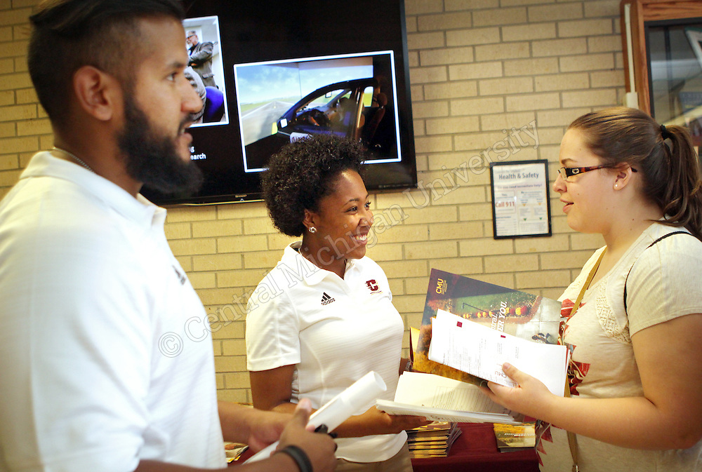 A student talks with faculty and staff members about scholarships during the College of Humanities and Social and Behavioral Sciences college day photo by Emily Mesner