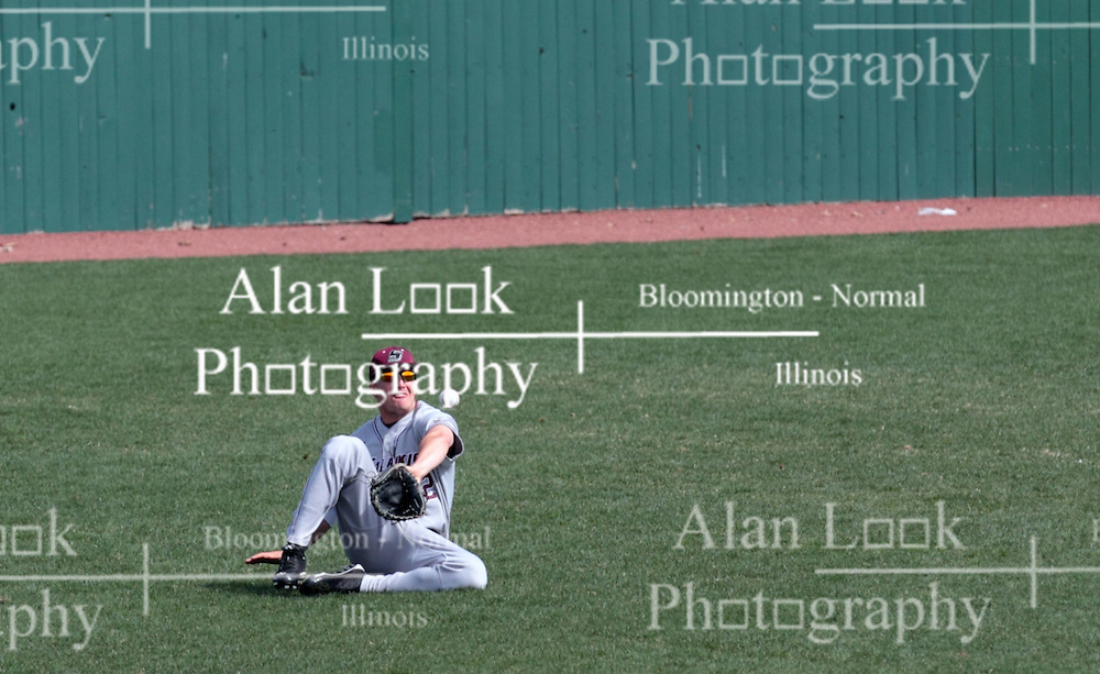 26 April 2014:  Tyler Rolland slides across the outfield grass to make a play on a hit ball during an NCAA Division 1 Missouri Valley Conference (MVC) Baseball game between the Southern Illinois Salukis and the Illinois State Redbirds in Duffy Bass Field, Normal IL