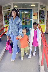 Single mother collecting young daughter and son from primary school,