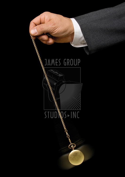 Man's hand holding a pocket watch and swinging it in the fashion of a hypnotist on a black background