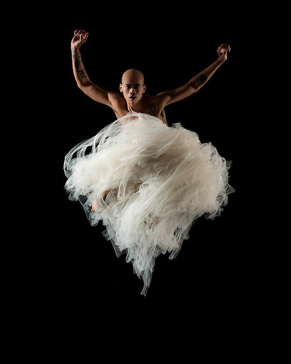Contemporary male dancer, Terk Lewis, jumping in a white tutu, taken in the photo studio on a black background. Photograph taken in New York City by photographer Rachel Neville.