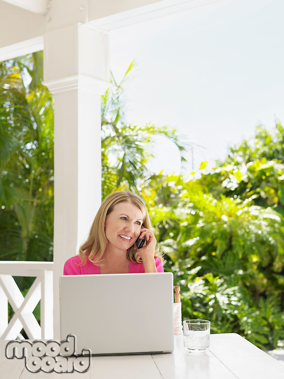 Woman using mobile phone sitting at verandah table with laptop