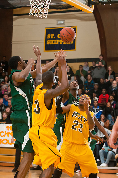Lathan Goumas | MLive.com..February 22, 2012 - Walter Davis(33) and Ralph Eason(23) of the Mott Community College Bears fight members of the Oakland Community College Raiders for control of the ball during a game at the Ballenger Field House in Flint on Wednesday. Mott defeated Oakland 60-58.