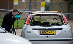 ©  London News Pictures. 15/10/2012. Harlow, UK. A fire investigation team photographing a burnt out car at the scene on Barn Mead, Harlow, Essex where three children and a woman have died and three others are in hospital following a house fire. Two boys aged 13 and six, a girl aged 11 and the woman were declared dead at the scene. A nine-year-old boy and a three-year-old girl have serious burns and a man has minor burns. Photo credit : Ben Cawthra/LNP