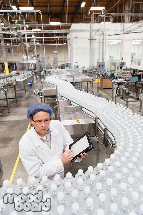 High angle view of man examining bottles at bottling plant