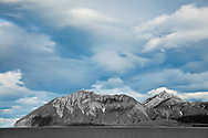 Dramatic evening light and clouds above Mount Chinitna and the Chigmit Mountains of Iniskin Peninsula along Chinitna Bay and Cook Inlet in Lake Clark National Park in Southcentral Alaska. Summer. Evening.