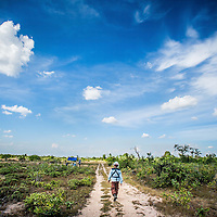 Cambodia has been dealing with the insurmountable task leftover from decades of war and its legacy, unexploded ordnance or UXOs. Estimates range from 3 to 9 million unexploded bombs that are still just beneath the surface throughout the region. These bombs are left over from air strikes, artillery fire, mortar shells, rockets, grenades, anti-personnel and anti-vehicle land mines are indiscriminate weapons and do not expire, often killing or injuring between 100 to 200 people in Cambodia a year. With little resource, the countries' people and Non Governmental Organizations (NGOs) are still facing over a hundred years being exposed to this deadly issue while walking and cultivating their land in fear.<br /> <br /> Cambodian Mine Action Centre (CMAC) worker clad in protective gear donated by the Japanese prepares to search for land mines and unexploded ordnance using a metal detector to sweep a field in the Cambodian countryside province of Kampong Thom. Jan. 2013.