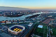 Nederland, Zuid-Holland, Rotterdam, 07-02-2018; Rotterdam-Zuid, deelgemeente Feijenoord met het stadion van voetbalclub Feyenoord. In stadion 'De Kuip' branden groeilampen om het gras ook in de winter te laten groeien.<br /> Het Eiland van Brienenoord en Van Brienenoordbrug in de achtergrond. Rechts van flats op de oever van de Nieuwe Maas komt in de toekomst de Sport Campus Stadionpark. Op dit sportpark komt ook het nieuwe stadion, 'de nieuwe Kuip aan de Maas'. <br /> <br /> Feijenoord, stadium 'De Kuip' of the football club Feyenoord to Marathonweg (r) with grow lights.<br /> <br /> luchtfoto (toeslag op standard tarieven);<br /> aerial photo (additional fee required);<br /> copyright foto/photo Siebe Swart