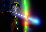 Man with glowing bow and arrow.Black light