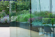 View through glass doors, salvia, nepeta, gaura and eryngium in powder-coated steel raised bed