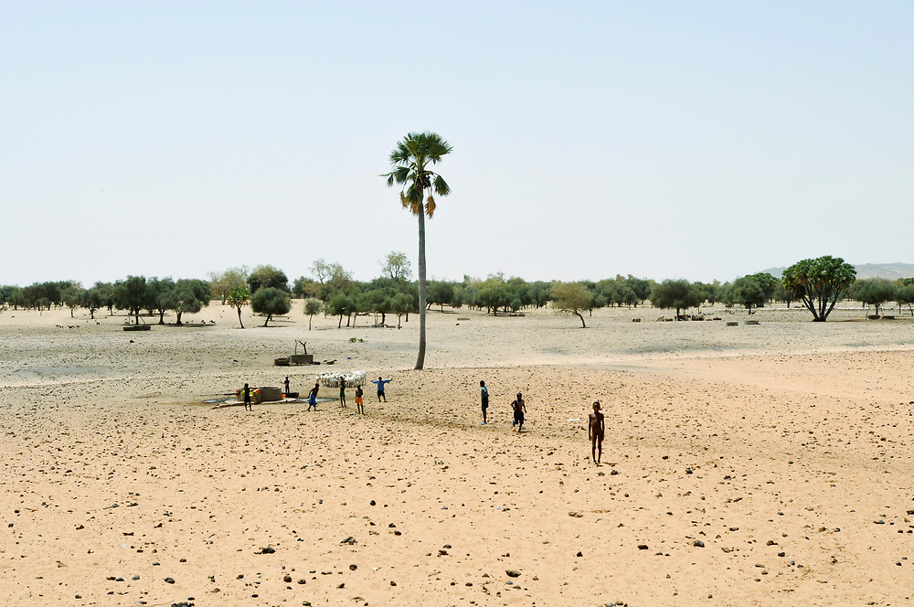 Children gather at a watering hole used for migrating herds of sheep, cattle and camels during the dry season in the Guidimakha province of Mauritania. Only a few decades ago the vast majority of Mauritania's population were nomadic herdsmen. While the population remains mobile and livestock play an important roll in the culture and daily life of Mauritanians, in recent years the society has become increasingly sedentary, relying on agriculture for sustenance. Global warming and climate change have caused rainy seasons to fail and prolonged drought throughout the Sahel, drastically reducing grazing ares, ruining harvests, causing wide spread food insecurity and contributing to large-scale migration from rural areas to cities and abroad.<br /> Guidimakha, Mauritania. 09/03/2011.