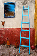 A blue ladder leans against a wall in the narrow alleyways of Essaouira, Morocco.
