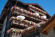 Multi-colored flower boxes on old wood buildings. Zermatt, in the Pennine Alps, Switzerland, Europe.