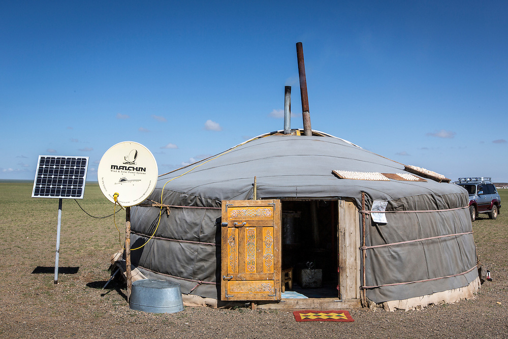 A ger camp complete with solar power and a satellite dish is set up in the Gobi desert of Mongolia on July 28, 2012.  The ger is a circular tent made out of felt and a collapsible frame and used as the family home by the nomadic herdsmen of Mongolia. Common families are four to five people. © 2012 Tom Turner Photography.