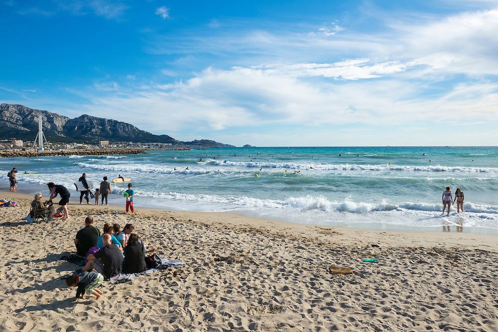 People enjoy the beach at 6:30 p.m. in Marseille, France. On the left is the ferris wheel beside Plage Bonneveine.