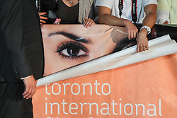 Fans unfurl a poster that shows the eyes of Penelope Cruz ahead of the  'Twice Born' premiere during the 2012 Toronto International Film Festival at Roy Thomson Hall, September 13th 2012. Photo by David Tabor/ i-Images.