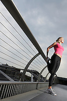 Woman stretching on foot bridge low angle view Millennium Bridge London England