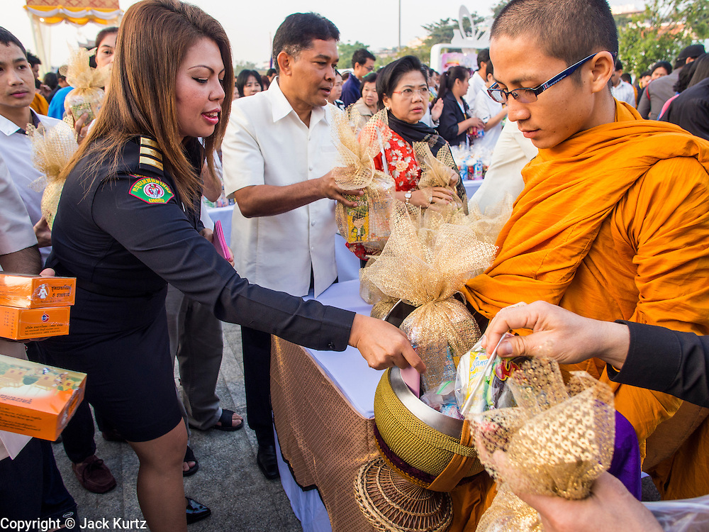 01 JANUARY 2014 - BANGKOK, THAILAND:  People make merit by presenting offerings to Buddhist monks at Bangkok City Hall. Several thousand people, mostly Bangkok city officials, gathered on the plaza of Bangkok City Hall Wednesday for the traditional New Year merit making ceremony.    PHOTO BY JACK KURTZ