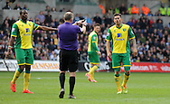 Bradley Johnson of Norwich City has a word with referee Jonathan Moss while Captain Sebastien Bassong (l) tries to calm the situation.<br /> Barclays premier league match , Swansea city v Norwich city at the Liberty stadium in Swansea, South Wales on Saturday 29th March 2014.<br /> pic by Phil Rees, Andrew Orchard sports photography.