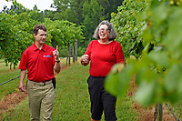 Backyard Road Farm & Vineyard's Deborah Price (right) laughs as Vance County extension agent Paul McKenzie shares a story while visiting her vineyard outside Henderson.